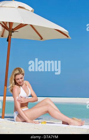 Woman Applying Sun Lotion On Beach Holiday - Stock Photo