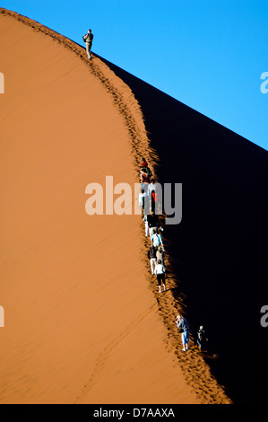 Tourists climbing giant sand dunes Dune 45 at Sossusvlei Namib Desert Namibia - Stock Photo