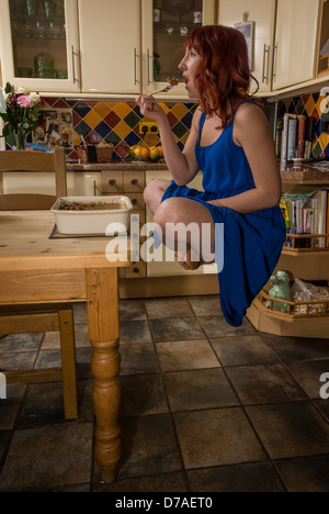 Red headed girl eating at a table and levitating over table in kitchen