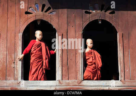 Two young monks by the window in Shwe Yaunghwe Kyaung Monastery near to Lake Inle, Myanmar - Stock Photo