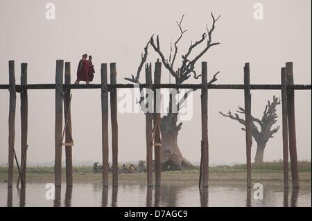 Three Buddhist monks walk across the U Bein Bridge on the Taungthaman Lake in Amarapura, Myanmar, 02 April 2013. - Stock Photo