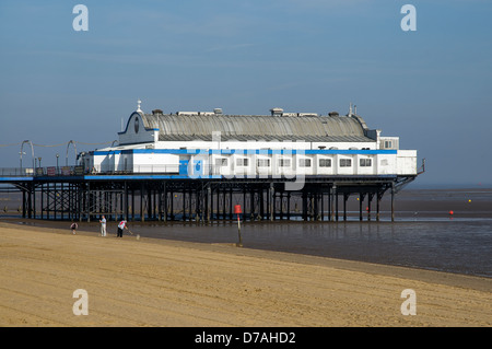Two adults and a child play cricket on the beach in front of Cleethorpes Pier, North East Lincolnshire, United Kingdom. - Stock Photo