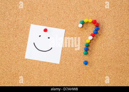 Smile note pinned to cord board. Question mark made of pushpins - Stock Photo