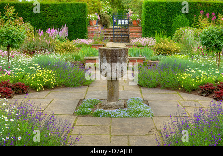 Flagged formal garden with a stone vase ornament and summer flowers. - Stock Photo