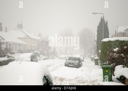 A snowbound street in Lincolnshire UK, showing deep lying snow on the road and pavement (sidewalk). Bad poor weather - Stock Photo