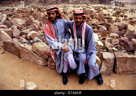 Twin Bedouins wearing a red and white checked keffiyeh and traditional robes in Wadi Rum desert known also as the - Stock Photo