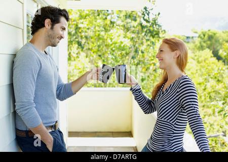 A Man And Woman Toast Each Other With Their Coffee Mugs;Wailua Kauai Hawaii United States Of America - Stock Photo