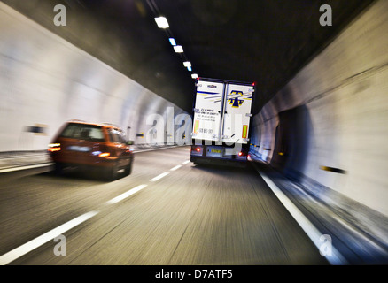 a car passes a truck in a highway tunnel - Stock Photo