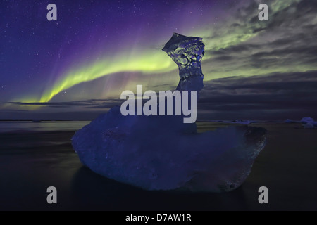 Aurora borealis dances over iceberg from the glacial lagoon jokulsarlon; iceland - Stock Photo
