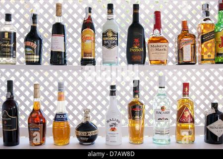 Colorful liquor bottles on a shelf at a beach bar in Ibiza - Stock Photo