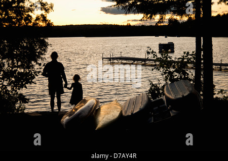 Father And Daughter Watch A Sunset On Beech Hill Pond;Otis Maine United States Of America - Stock Photo