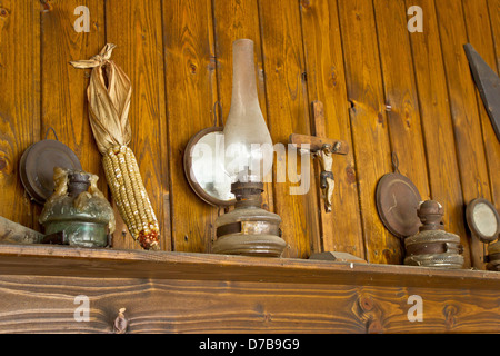 Old lantern, crucifixion, corncob and paraffin lamp on shelf, with wooden background - Stock Photo