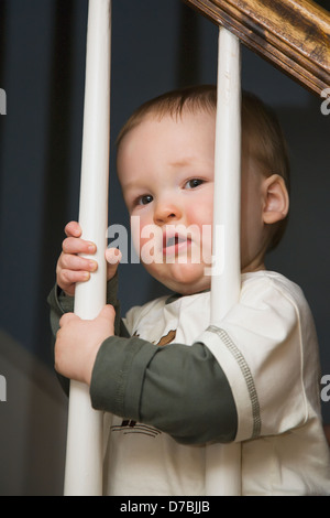 A baby boy holds on to the stair rail balusters with both hands;Willimantic connecticut united states of america - Stock Photo
