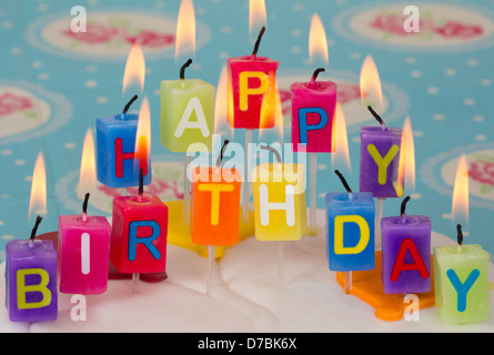 Happy Birthday candles on birthday cake with blue and floral background. - Stock Photo