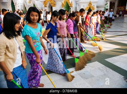 Women Buddhists sweeping the pagoda floor, Shwedagon Pagoda, Yangon, Burma (Myanmar) - Stock Photo