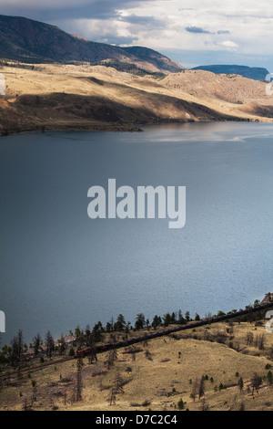 A small train makes it's way along the shore of kamloops lake;Kamloops british columbia canada - Stock Photo