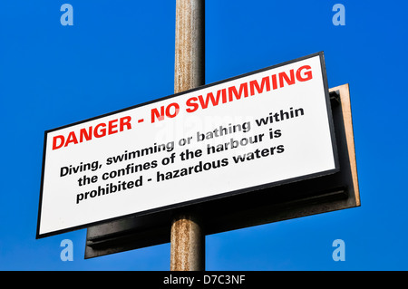 Sign at a harbour warning against swimming due to hazardous waters - Stock Photo