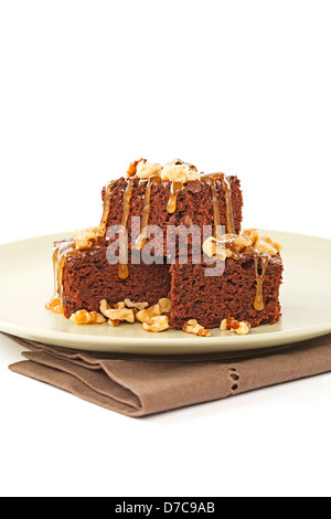 Brownies topped with nuts and caramel on plate - Stock Photo