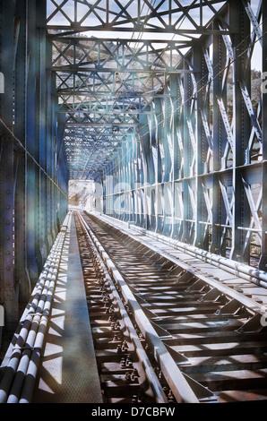 Blue metal bridge on the railroad tracks - Stock Photo