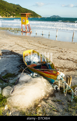Boat and fishing net on the sand at Pantano do Sul Beach. - Stock Photo