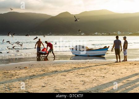 Fishermen and fishing boat on the sand at Pantano do Sul Beach. - Stock Photo