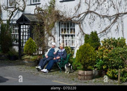Elderly couple sitting on bench, with dog, Hawkshead, Lake District National Park, Cumbria, England UK - Stock Photo