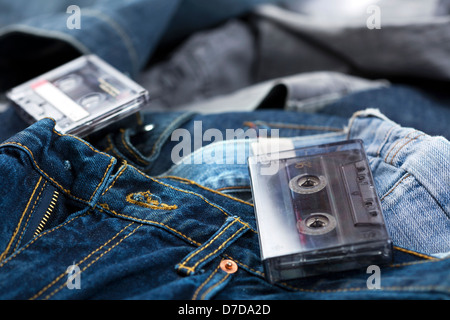 A couple of blank audio cassettes, one of them still in its box, laid on the background of various pairs of jeans - Stock Photo