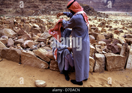 Bedouins wearing a red and white checked keffiyeh and traditional robes in Wadi Rum desert known also as the Valley - Stock Photo