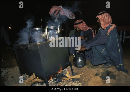 Bedouins nomads wearing a red and white checked keffiyeh brewing tea in Wadi Rum desert known also as the Valley - Stock Photo