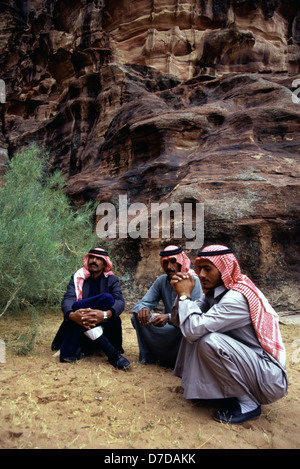 Bedouins wearing a red and white checked keffiyeh at a sandstone ravine in Khazali Canyon in the desert of Wadi - Stock Photo