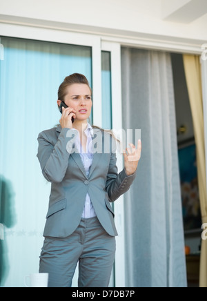 Business woman talking mobile phone on terrace - Stock Photo