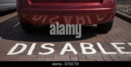 Disabled car parking space, with reversed reflection in car bodywork, Darlington, North Yorkshire, UK - Stock Photo