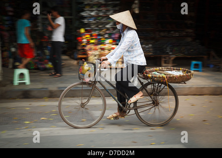A street vendor on her bicycle in the Old Quarter of Hanoi, Vietnam - Stock Photo