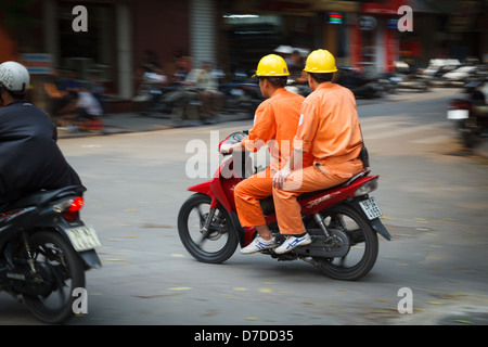 Two engineers (male) on a scooter in the Old Quarter, Hanoi. - Stock Photo