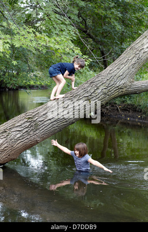 sisters playing and swimming in creek - Stock Photo