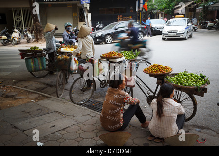 Street vendors selling their fruit from their bicycles in the Old Quarter of Hanoi, Vietnam - Stock Photo