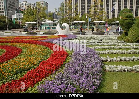 Park with flowers and Seoul's symbol Haechi at Sejongno street / Jongno-gu in downtown Seoul, South Korea, Asia - Stock Photo