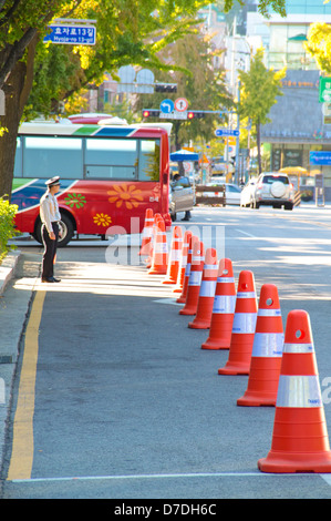 Traffic control cone and traffic officer on a korean street. - Stock Photo
