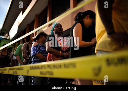 Kuala Lumpur, Malaysia. 5th May, 2013. Malaysian voters wait in line to cast their ballots outside a polling station - Stock Photo