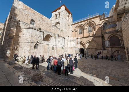 Church of the Holy Sepulcher in Jerusalem with tourists and pilgrims outside - Stock Photo