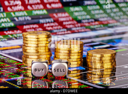 Stacks of coins, dices cubes with the words SELL BUY and down trend chart with the columns of figures as the background - Stock Photo