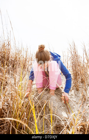 girl sitting on beach dune - Stock Photo