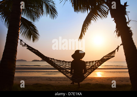 silhouette of woman in hat sitting in hammock at sunset on the beach - Stock Photo