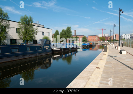 Canal narrowboats reflected in the Cotton Field Park marina, New Islington, Ancoats, Manchester, England, UK - Stock Photo