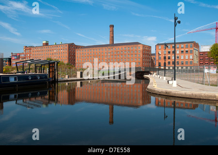 Former cotton mills, now apartments, reflected in the Cotton Field Park marina, New Islington, Ancoats, Manchester, - Stock Photo