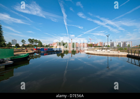 Cirrus cloud and former cotton mills reflected in the Cotton Field Park marina, New Islington, Ancoats, Manchester, - Stock Photo
