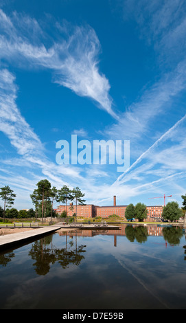Cirrus clouds and former cotton mills reflected in the Cotton Field Park marina, New Islington, Ancoats, Manchester, - Stock Photo
