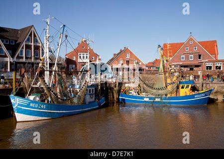 Fishing boats and shrimp boats in the old fishing port of Neuharlingersiel, East Frisia, Lower Saxony, Germany - Stock Photo