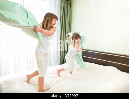 Little girls fighting using pillows in bedroom - Stock Photo