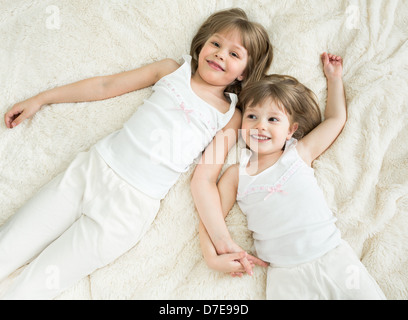 happy little sisters lying on back top view Stock Photo